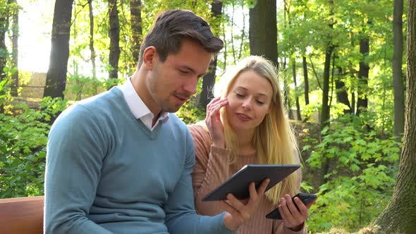 Thumbnail for A Young Attractive Couple Works on a Smartphone and a Tablet on a Bench in a Park on a Sunny Day