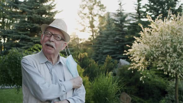 The Senior Man Takes Off Medical Mask Exhales and Talks with Smile Outdoors