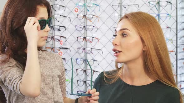 Thumbnail for Pretty Little Girl Shopping for Sunglasses with Her Beautiful Mother
