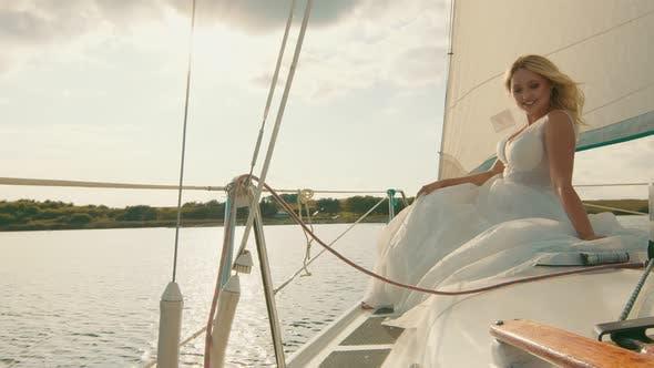 Braut auf einer Yacht bei Sonnenuntergang. Der Blick der Braut in der Ferne, die Sonnenstrahlen