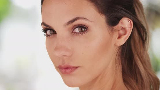 Thumbnail for Stunning young brunette staring intimately at camera on bright serene background