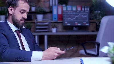 Businessman Late Night in the Office Scrolling on the Phone