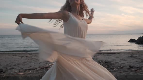 Thumbnail for Attractive Girl Dancing on the Beach in a Fluttering Dress.