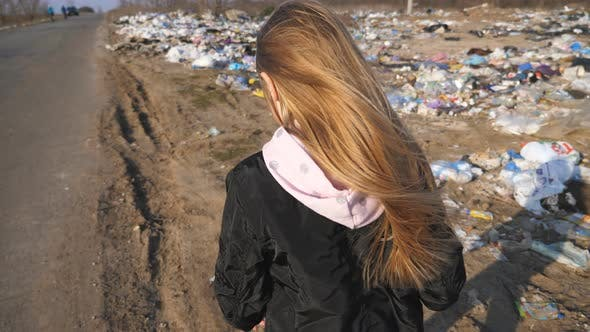 Thumbnail for Little Girl Goes on the Road Against the Background of Garbage Dump. Small Female Child with Blonde