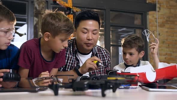 Cover Image for Asian Electronic Engineer with Caucasian Schoolchildren Working in Modern School
