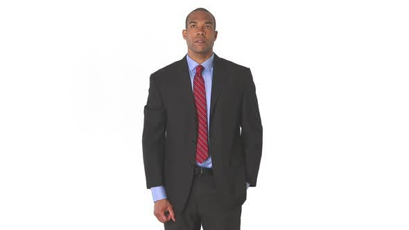 Young executive with suit looking up while standing
