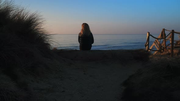 Thumbnail for Shot of a Woman Sitting on a Log Overlooking the Beautiful Coast of Denmark