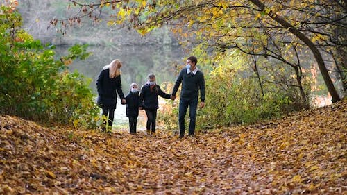Family Parents with Children in Medical Masks Walk in the Park on an Autumn Day