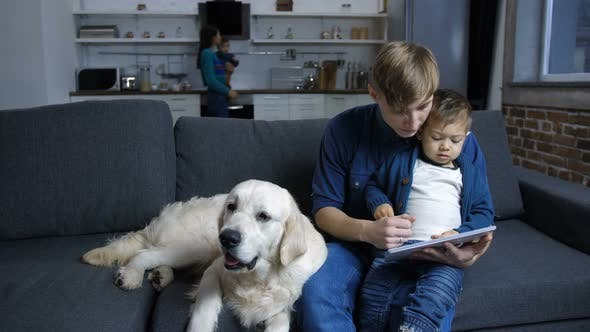 Thumbnail for Father and Toddler Boy with Dog Bonding on Couch