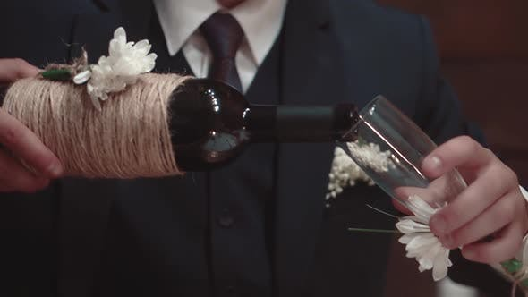 Cover Image for Young Man Pours Wine Into a Glass in a Restaurant, Close-up, Slow Motion