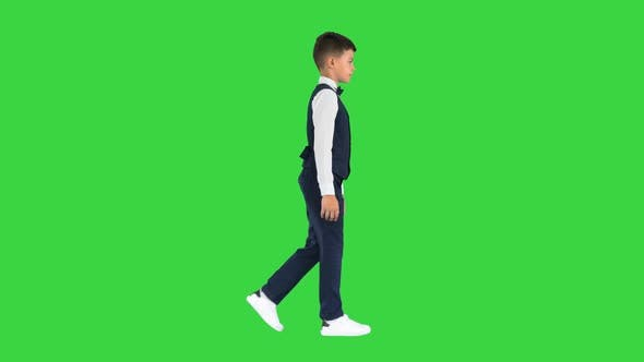 Little Boy Weste Fliege Gehen Blick Straight Ahead Green Screen Chroma Key