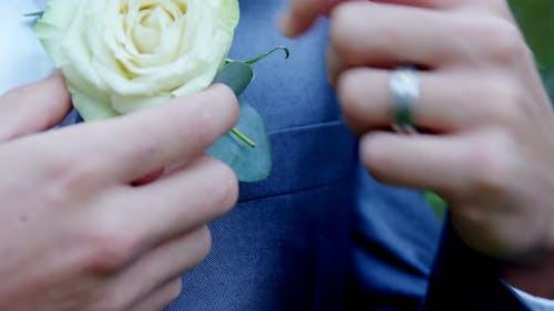 Groom adjusting rose on his blazer