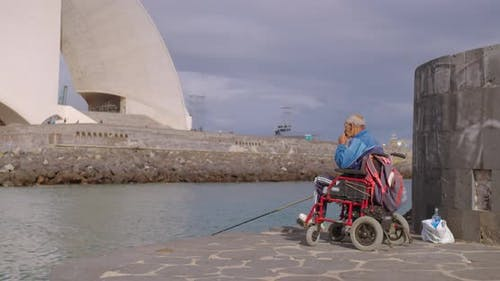 Handicapped Fisherman in a Wheelchair Fishing From a Handicapped.