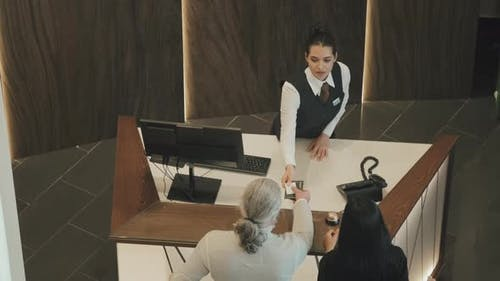 Top-View of Couple Checking-In at Reception Desk