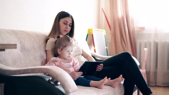 Cover Image for Side View, : Young Attractive Mother and Sweet Daughter Are Sitting on the Couch and Training