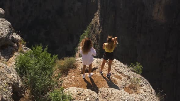 Friends Stand on Rock Looking at Gap Between Old Mountains