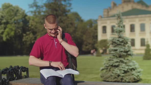 Thumbnail for Busy Male Student Answering Phone Sitting on Bench