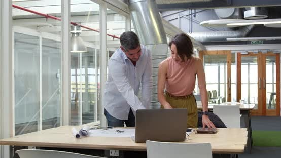 Thumbnail for Business people discussing over blueprint in modern office