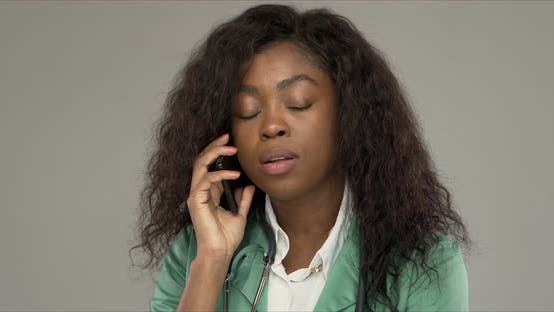 Displeased Black Doctor Answering Phone Call