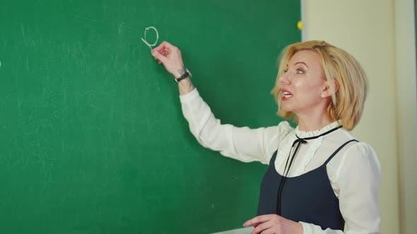 Schöner Lehrer schreibt an eine Tafel
