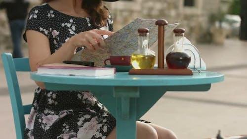 Schöne weiblich sitzend auf straße cafe tisch mit gepäck, Prüfung stadt karte