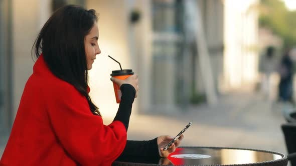Thumbnail for Fashionable Attractive Woman Drinks Coffee and Uses a Smartphone Sitting at a Table in a Cafe