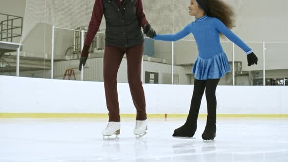 Thumbnail for Little Girl in Dress Skating on Ice with Coach
