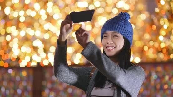 Thumbnail for Woman look at mobile phone over christmas light decoration