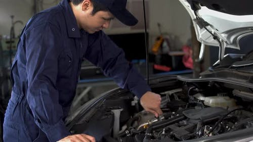 male mechanic using wrench to repair engine, car service