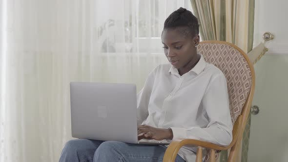 Thumbnail for Attractive Afican American Woman Focused Working with Her Up To Day Laptop Sitting on Armchair in