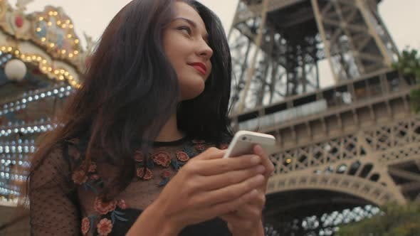 Thumbnail for Travel Woman Using Smartphone Looking on Map Near the Eiffel Tower and Carousel, Paris