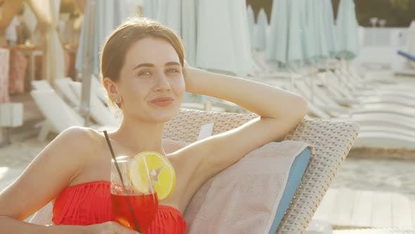 Thumbnail for schöne junge frau schlürfen cocktail während sonnenbaden am strand