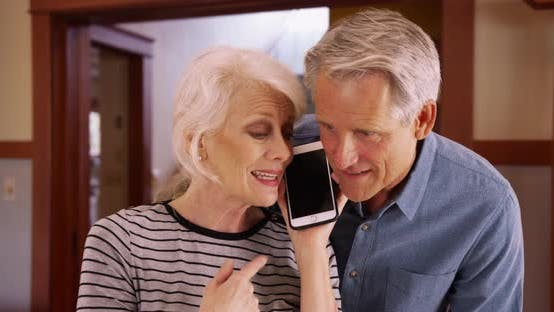 Thumbnail for Senior couple talking on smartphone at home