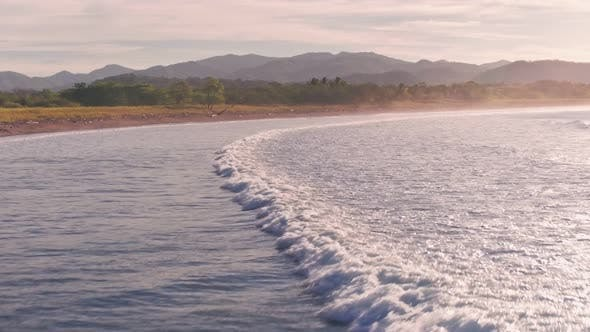 Pelicans flying at Playa Buena Vista Beach at sunset, Costa Rica, Aerial drone view