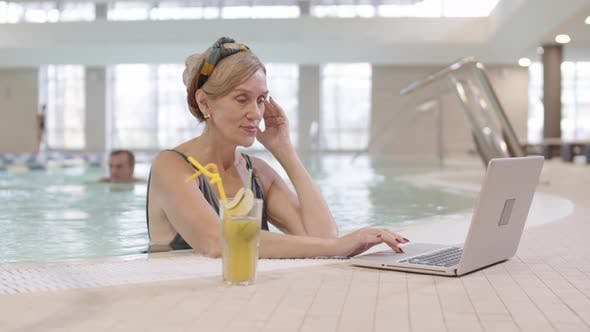 Thumbnail for Businesswoman Using PC while Standing in Pool