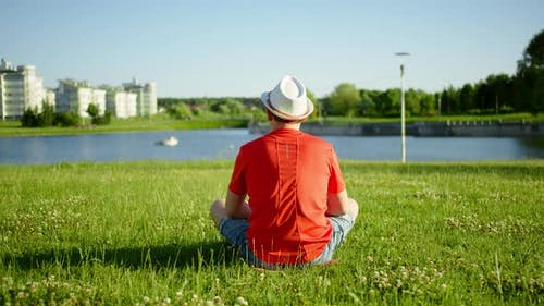 A Man Sits on the Grass, Looks at the Pond, Camera Movement, Back View