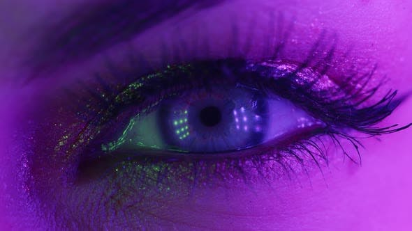 Thumbnail for Extreme Close Up of Human Eye Iris Under Neon Light . Female with Beautiful Makeup, Glitter Shadows