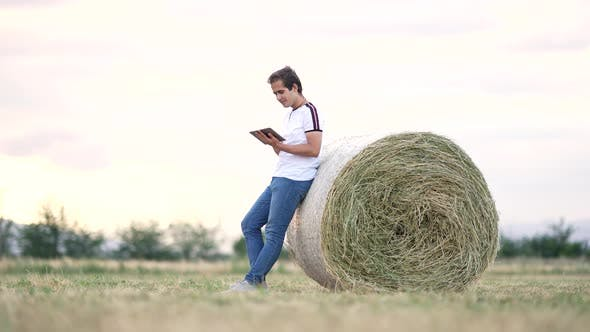 An agricultural engineer examines bales of hay.
