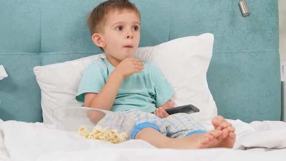 Little Boy in Pajamas Eating Popcorn in Bed at Morning and Switching Cartoons on TV with Remote