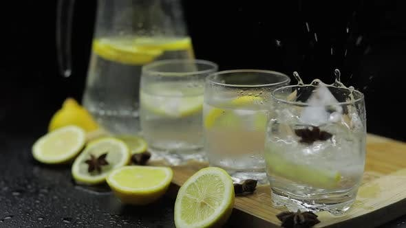 Eiswürfel zu Zitronensaft in Glas mit Zitronenscheiben geben. Alkoholischer Cocktail