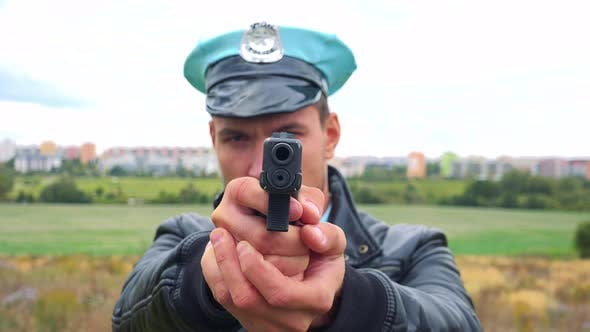 Thumbnail for A Young Police Officer Aims a Gun at the Camera