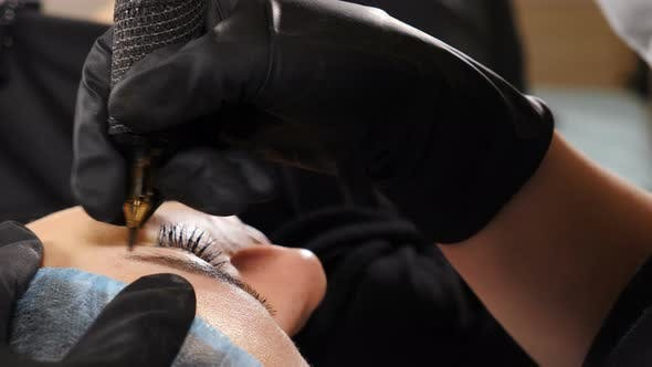 Beautician in Black Gloves Making Permanent Makeup Correction Eyebrows Shape