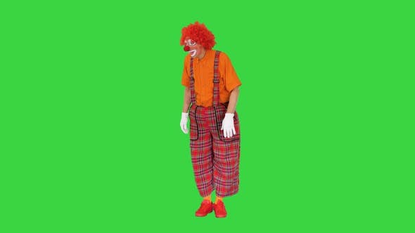 Actor Dressed As a Clown Looking for a Way To Act in a Funny Way on a Green Screen Chroma Key