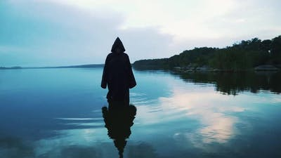 Scary figure in black mantle in the river. Halloween costume.
