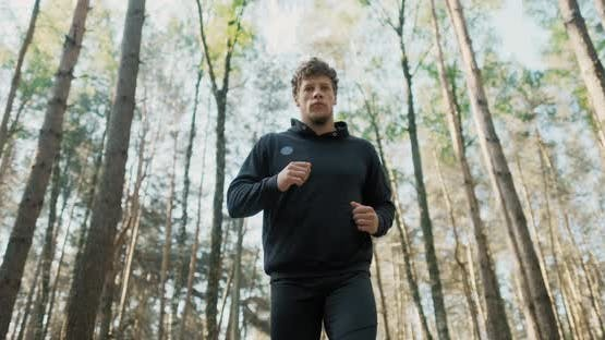 Slow Motion Shot of Man Running Through Pine Forest on Path in Woods. Runner Training Fitness