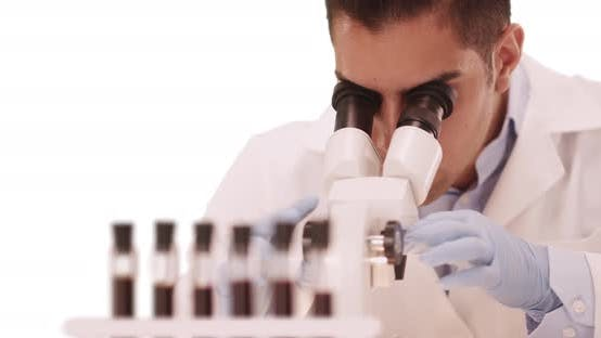 Thumbnail for Millennial Latino medical research scientist in lab using microscope
