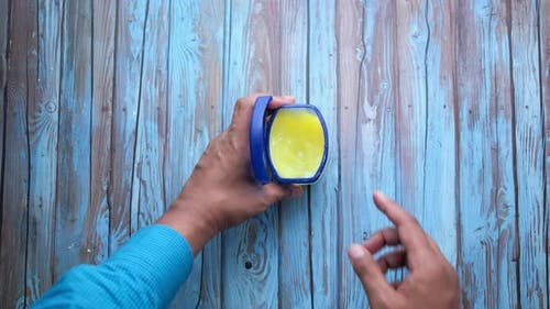 Man's Hand Using Petroleum Jelly Top Down