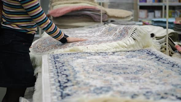 Woman Choosing Carpet in a Furniture Store