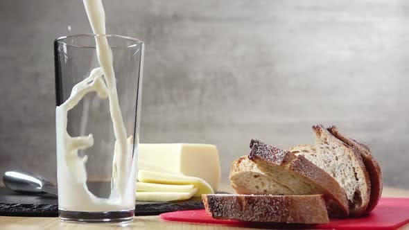 Thumbnail for Cheese and Bread and Milk is Poured Into a Glass