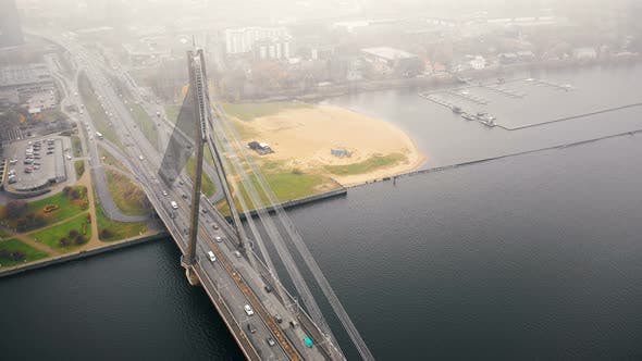 Thumbnail for Amazing Aerial Cityscape View, Traffic on Cable Bridge Over Daugava in Riga Old Town Under Thick Fog